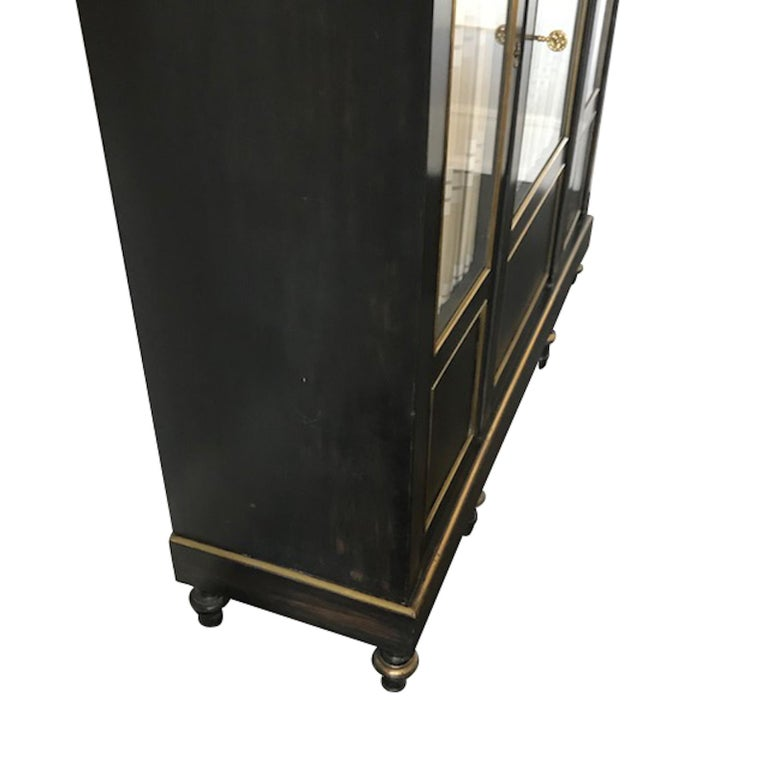 Pair of 19th century French Napoleon III ebonized black cabinets with decorative brass details. Original glass front panel doors. Three interior wooden shelves.