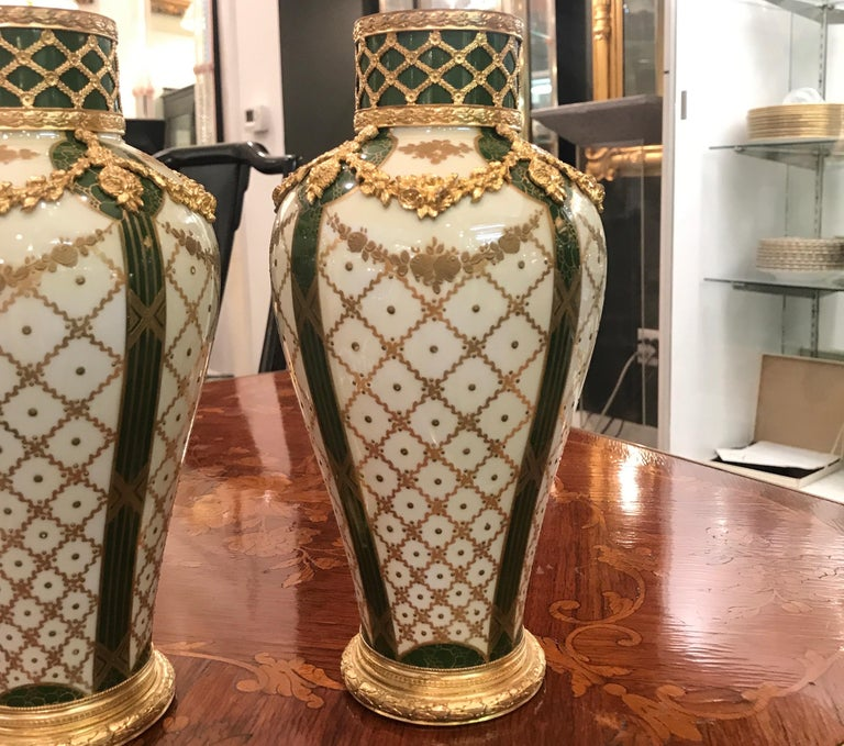Stunning pair of signed Sèvres hand painted French porcelain vases with gilt bronze mounts. The necks with gilt bronze over green porcelain with a bulbous shoulder with a gilt bronze swag all around. The body with a gilt lattice work decoration with