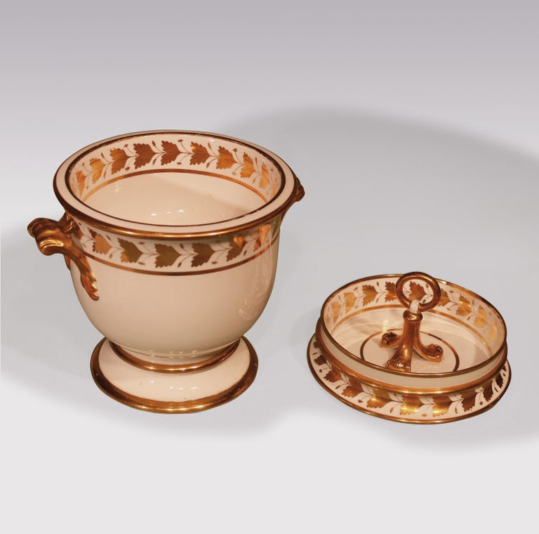 An early 19th century pair of porcelain ice-pails with gilt leaf decorated borders, part of a dessert service, comprising 20 plates, 3 shell dishes, 3 circular dishes, 4 oval dishes, 1 comport and a pair of ice-pails.