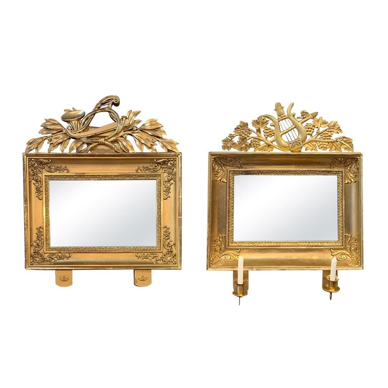 An antique pair of Swedish mirrors made of hand crafted gilded wood and mirrored glass with two candleholders, the original glass is in good condition. Wear consistent with age and use, Circa 1840, Sweden, Scandinavia.