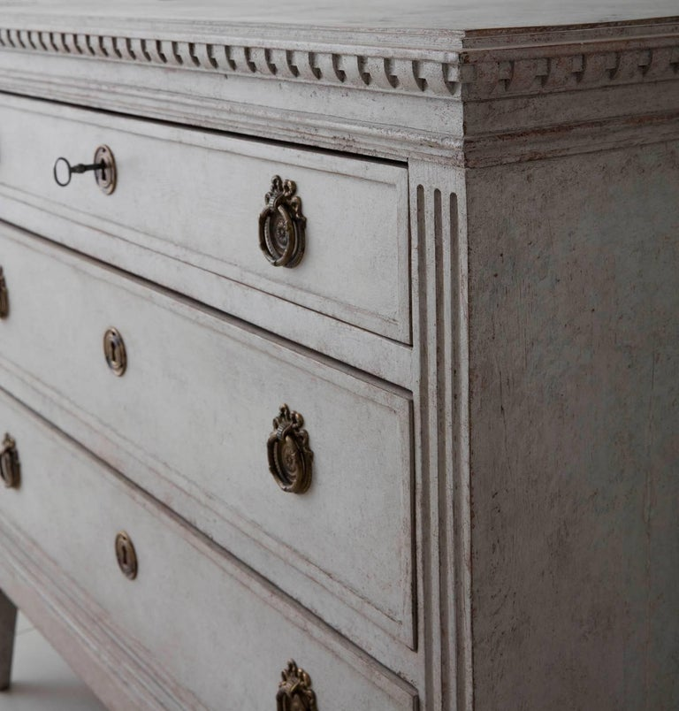 An elegant neoclassical pair of Swedish painted commodes in the Gustavian style. Each chest has three drawers, brass hardware, and original locks and keys. The hand-painted marbleized top is framed by dentil molding. The sides are fluted and the