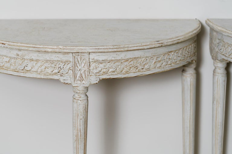 A pair of Swedish original paint demilune console tables in the Gustavian style. Beautiful carved guilloche pattern on the apron and carved rosettes above tapered and fluted legs.