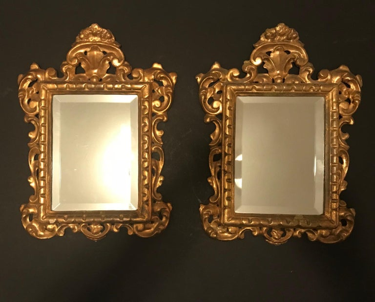 This is a pair of Venetian giltwood mirrors. The rectangular mirror plates are within a boldly carved scrolling acanthus frame with a carved leaf crown piece. The elaborately carved frame has the original water gilding.