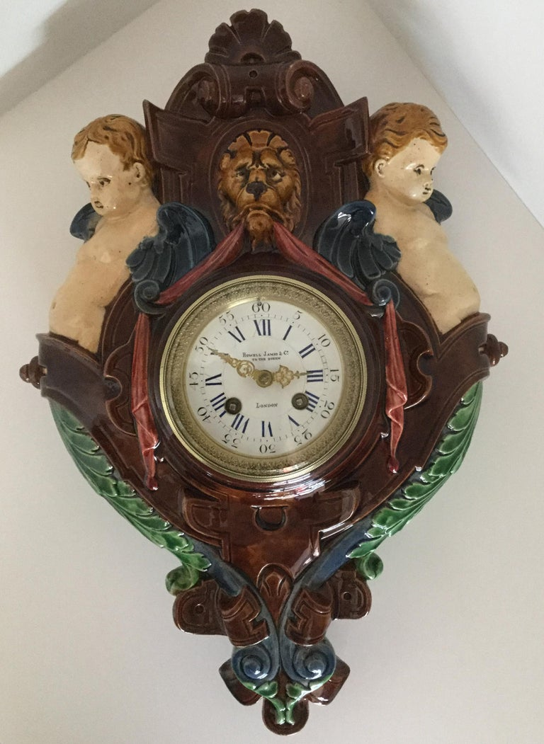A very rare decorative Palissy Ware Majolica 8 day striking wall clock, circa 1870, on multicolored ground, with green, cream, red, blue and brown decoration, surmounted by a lions head flanked by twin putti, with ribbon, leaf and scroll decoration,