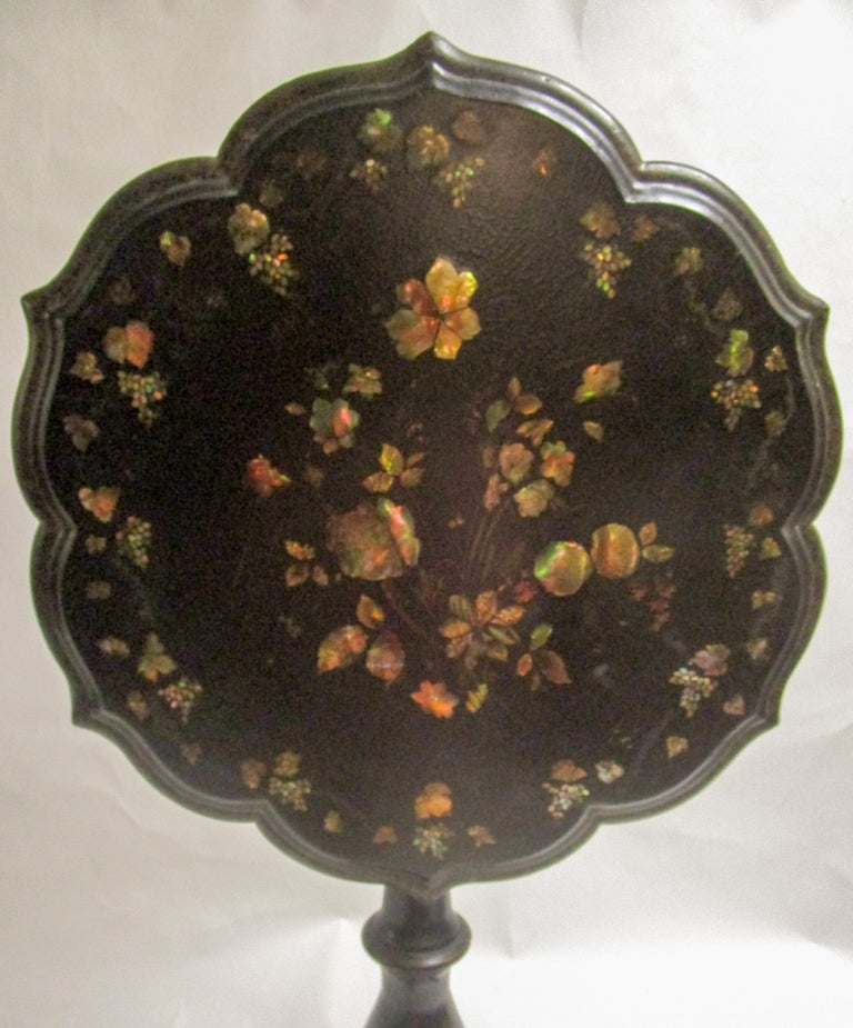 Large size English papier mâché japanned tilt-top gueridon with an intricate inlaid mother-of-pearl top done in a floral motif. The top is unusual because it features an intricate triple scalloped edge that comes to six points. The table is