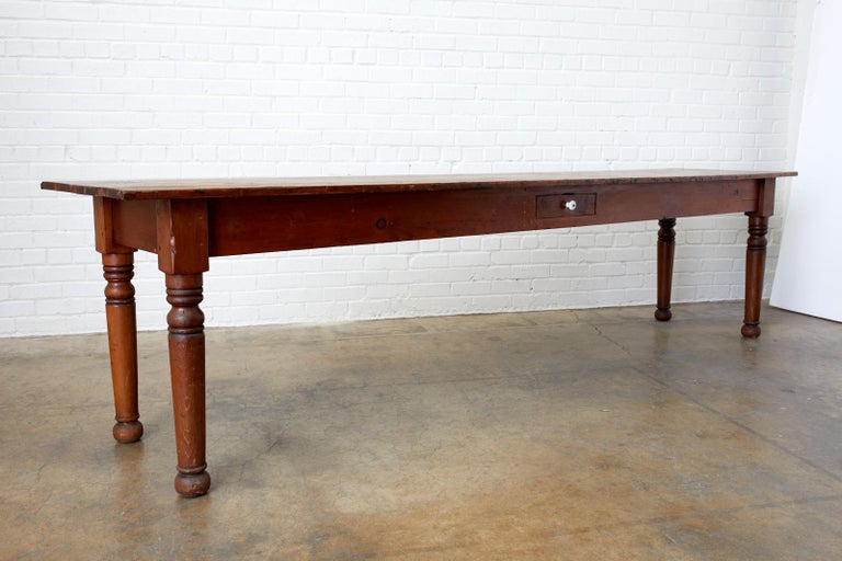 Large, rustic 19th century Pennsylvania Dutch American farmhouse table, harvest table, or work table. Features a nearly 10 foot long plank top that appears to be pine supported by thick turned legs with ball feet. The tables has a storage drawer in