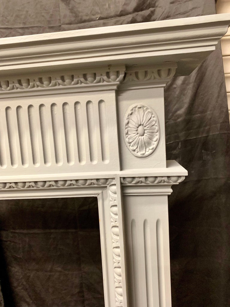 An elegant 19th century style period style carved painted wooden fireplace surround, a molded shelf sits above carved egg and dart cornice, with a projecting central tablet hosting a centralized shell with Pears and flowers, flanked by repeating