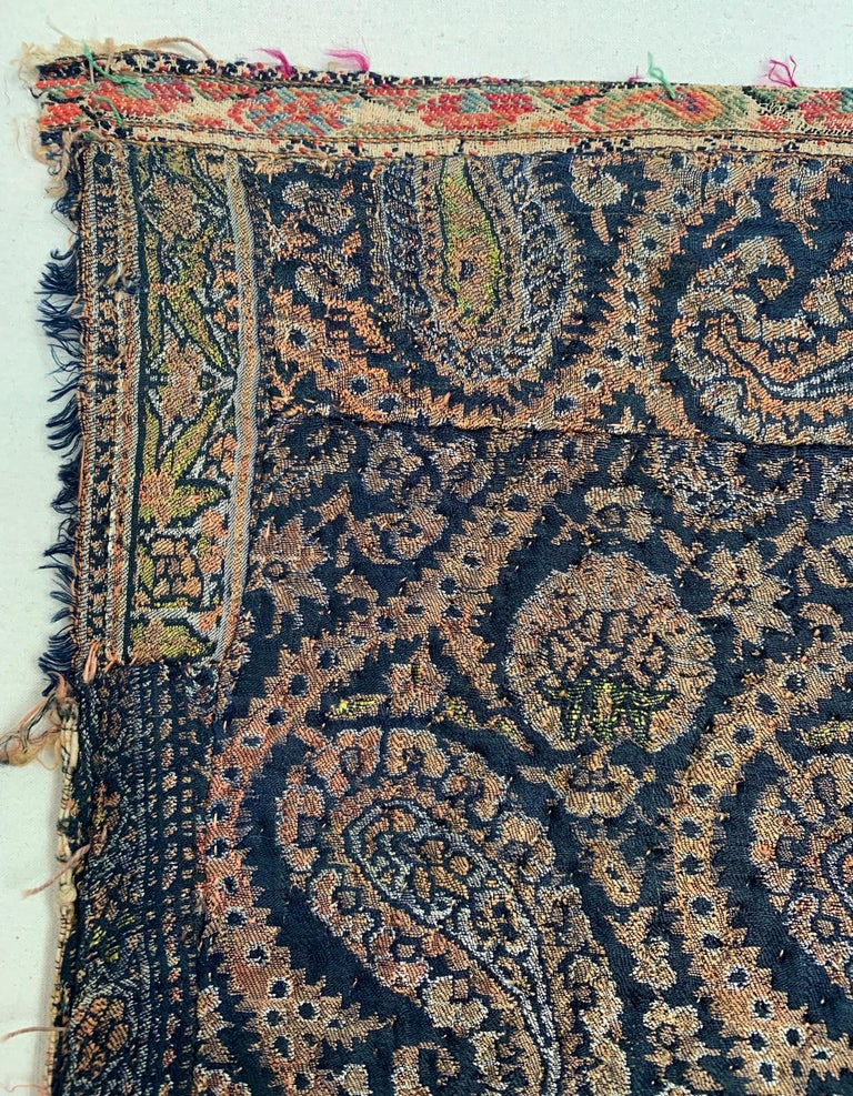 An 18th century Persian paisley jacquard-woven silk textile. Lightly quilted. Corner fragment of a much larger piece with right border attached by hand and lower edge finished with old Kashmiri shawl strip.
