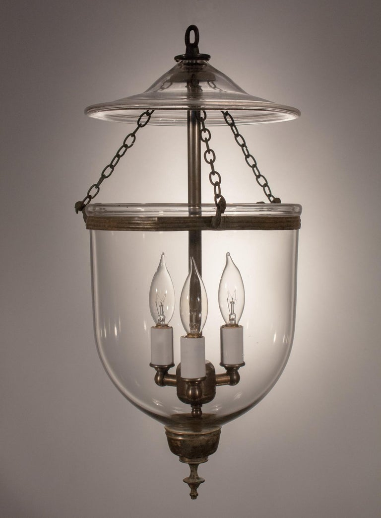 A simply lovely English bell jar lantern with its original chain, rolled brass band and finial candleholder base. This petite circa 1850 hall lantern features excellent quality handblown glass. It has been newly electrified with a three-bulb