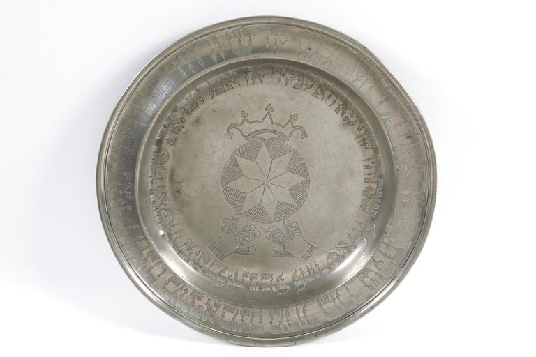 German Passover Pewter plate dated 1825. The plate with raised rim engraved in Hebrew with the Order of the Seder of Passover, In center, geometric design, surrounded by Hebrew text for the date and the owner's name, topped with a crown, and