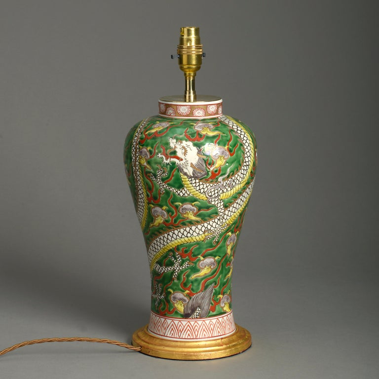 A late 19th century baluster form vase, the body decorated with a polychrome dragon upon a green glazed ground. Now mounted as a lamp and set upon a turned giltwood base.