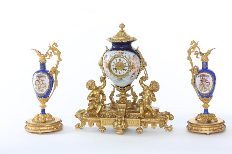 19th century Regency revival porcelain with gilt bronze mantel clock on stand with a pair of neoclassical revival ormolu mounted one handled amphora shaped ewers. The pieces are in great antique condition. Minor wear consistent with age / use. The