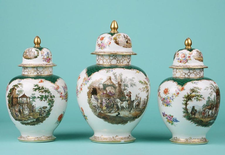 Set of three porcelain vases, painted with romantic scenes and floral motifs. The gold paint decoration has some wear here and there, appropriate to the age. The photos give a good impression of this. The vases are marked on the bottom with the