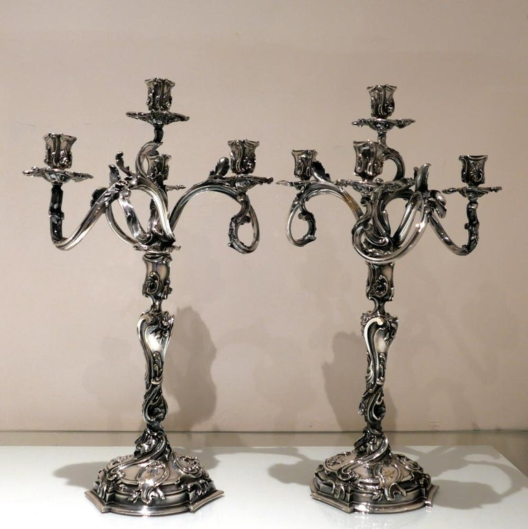 """An incredibly important looking and exceptional quality pair of four light """"Rococo"""" style French made candelabra decorated with elegant floral and foliate designs. The detachable bases have stylish contemporary engraved crests for importance."""