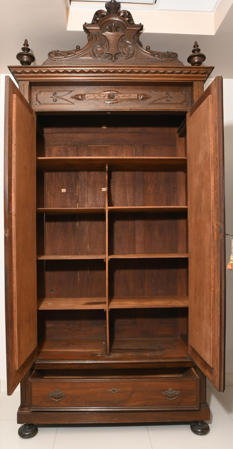 Dresser/Armoire from the Puerto Rican cabinetmaker Rafael Margarida who established his workshop in Old San Juan since 1892. The pediment has two inverted arcs that join to end in a crown. The center of the pediment is adorned with a carving