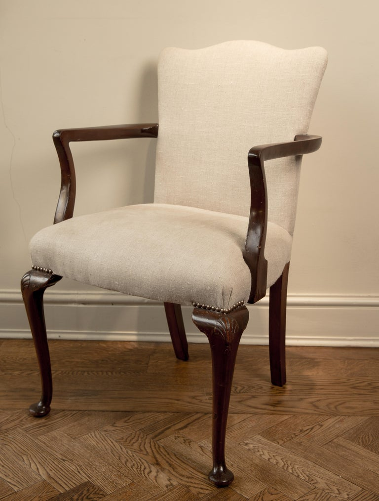 Charming camel back mahogany elbow chair in good original condition. With beautiful shell carving on its knees. Recovered in antique linen, inside upholstered in original horsehair.