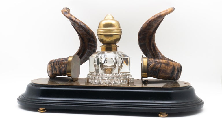 19th century ram's horn decorated inkwell, possibly Scottish. Comprised of a brass topped glass inkwell mounted on a brass and wooden oval base.