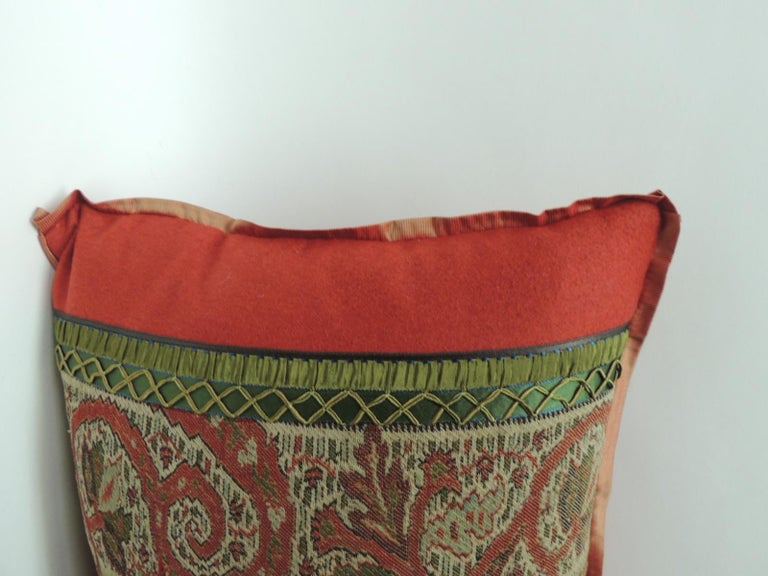 This pillow is made from the centre panel of a large antique Kashmir shawl. Framed with colorful paisleys on a dark background. Embellished with small tan color rope trim and textured brown linen backing. In shades of black, red, yellow, brown, tan