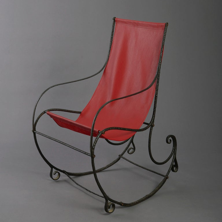 A Regency period cast iron rocking chair, having a rectangular back, with wrought iron scrolls to the arms and base. With red leather seat.