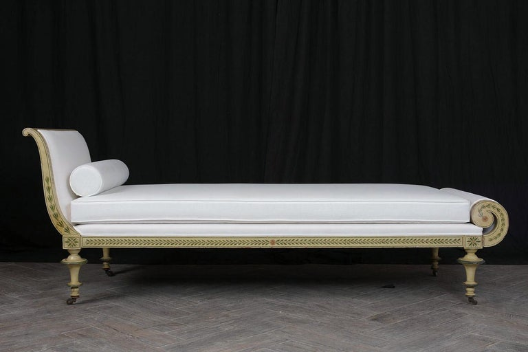 This 19th century carved painted Regency style chaise. It has original hand painted details adorning the frame, scrolled arms, and carved legs with original caster wheels feet in good condition. It has a single cushion and bolster pillow upholstered