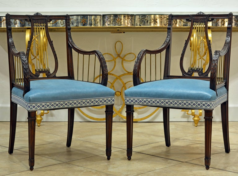 Dating to the late 19th century this elegant pair of Regency style armchairs features a carved mahogany frame with bronze accents in the lyre style back and armrests. They are attractively covered with pristine light blue chintz and trim.