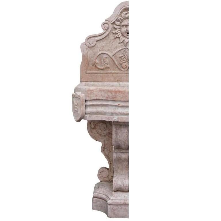 A wall fountain with a richly decorated backsplash depicting a sun mask and scrolls, set on a heavy basin with lateral shields and supported by an ornate scroll base.Hand carved in Rosso Verona marble. Wear consistent with age and use. Circa 1890