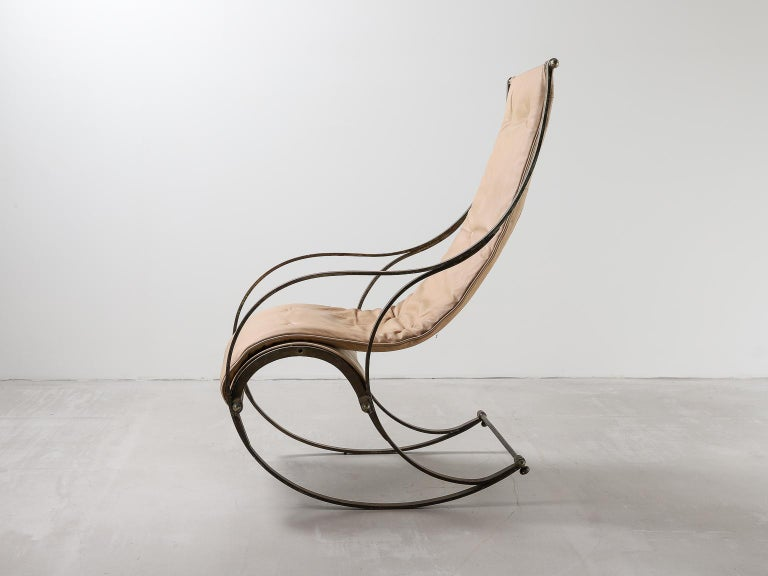 Rocking chair in bent steel with tan leather seat in the manner of R. W. Winfield. Chair rocking English 19th century black white, England. A stunning rocking chair made in England during the 19th century. Frame from cast iron. An off white canvas