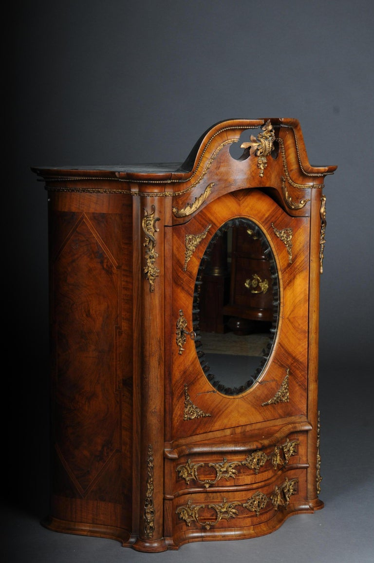 19th century Rococo top cabinet walnut root, Germany  Walnut root veneer on solid wood. Top cabinet with 2-drawer fronts above a door with medallion shaped mirror, faceted. Gold-plated fittings  (O-252).