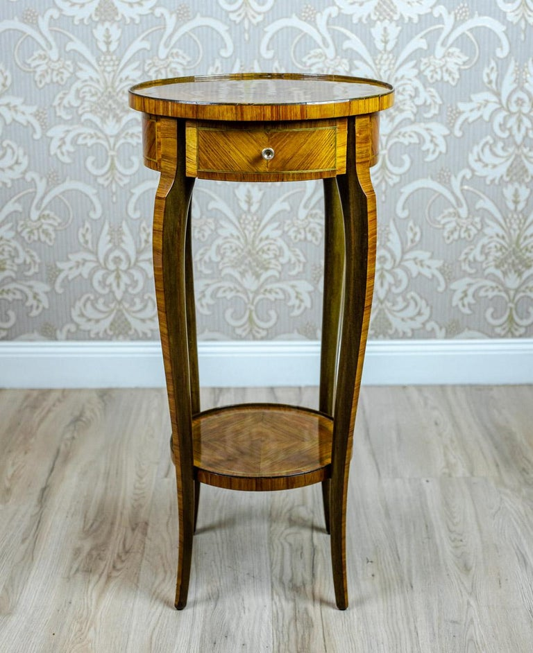 We present you a medium-sized end table/flower stand from the late 19th century. The tabletop is round; with a single drawer underneath it. This piece of furniture is supported on slender, slightly bent legs, which are joint together with a round