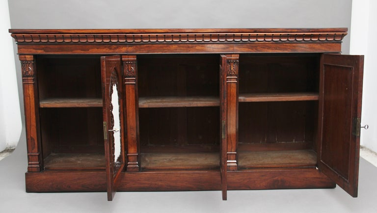 Early 19th century rosewood side cabinet, the wonderfully figured rectangular crossbanded top above a frieze with carved decoration, including three frieze drawers which are mahogany lined, below having three arch-panelled doors with fret-pierced
