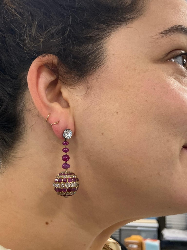 Antique ruby and diamond striped pave balls containing approximately 9 carats of old mine diamonds and 8.50 carats of rubies are suspended from a line of ruby beads totaling approximately 8 carats and collet set old mine diamonds totaling