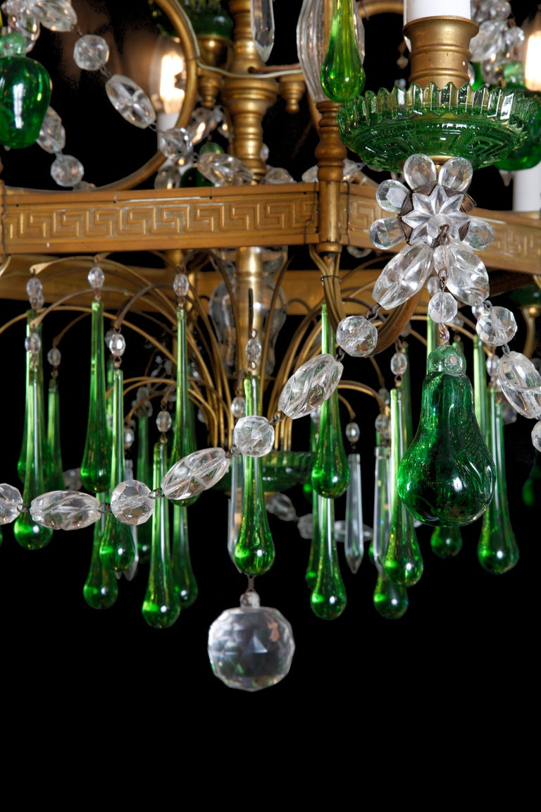 A Russian two-tier nine branch gilt bronze chandelier with a central hexagon frame supporting six arms beneath sweeping up to a further three arms on the central shaft, featuring green glass drip pans terminating at the top with a plume of two-tier