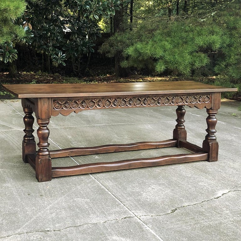 19th century rustic Country French farm table was hand-hewn from thick, solid planks of old-growth oak, and features massive turned legs on each corner supporting the apron, decorated on one side with stylized foliates carved directly into the wood.