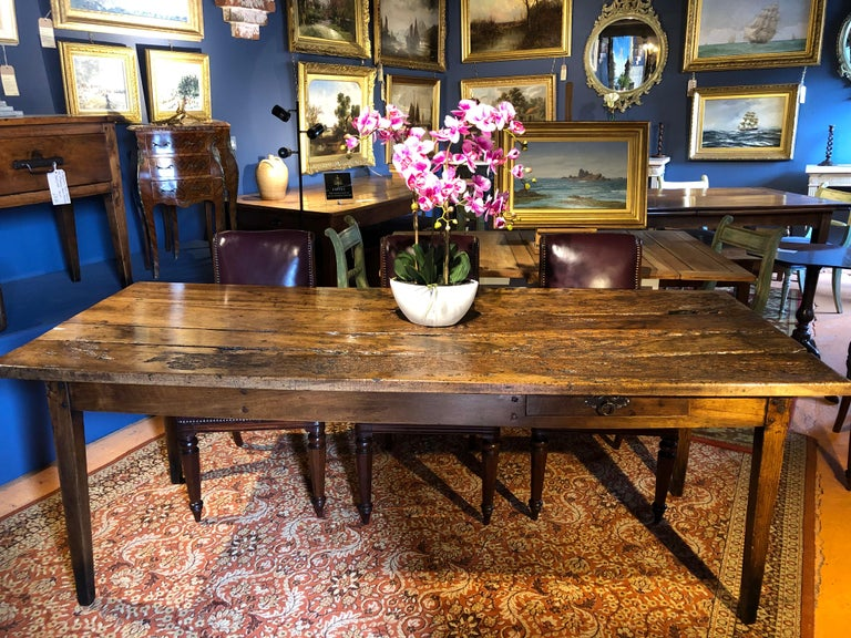 An incredibly rustic early 19th century French fruitwood (probably apple) farmhouse table. The top, naturally worn over the last 170 years this table has been reconstructed, sealed and re-polished by one of the top conservators of furniture in the