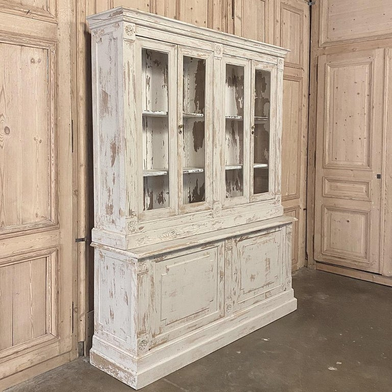 19th century Rustic French neoclassical bookcase is the perfect piece for displaying and storing your books, collectibles or family memorabilia! Four glazed doors on top create a visual framework for your display, while two cavernous cabinets below