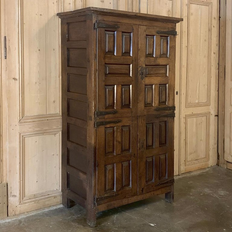 19th century rustic Spanish cabinet was built from local materials to last for generations, and features tailored raised panels and hand-forged iron hinges and hardware for a stunning casual effect. Heavy old-growth oak construction and