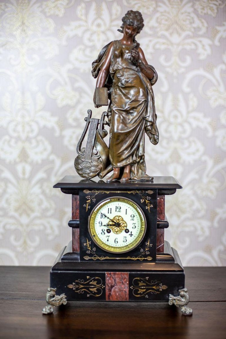 We present you a mantel clock with two candelabras. The case of the clock is made of two types of marble and topped with a brass figurine of a muse. Furthermore, the clock face, with Arabic numbers, is glazed, closed in a brass frame. The tension