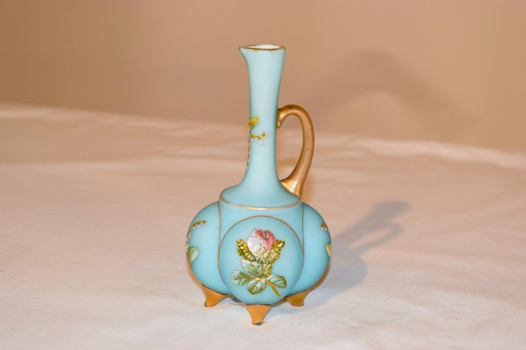 19th century satin glass cruet in a lovely blown form with applied glass handle and feet painted in gold. There are hand painted flowers on all sides.