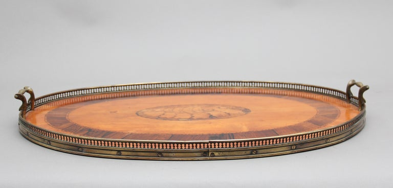 A decorative 19th century satinwood, brass and inlaid tray, the top crossbanded with inlaid shell decoration at the centre, having a pierced brass gallery running around the edge and brass carrying handles either end, circa 1880.