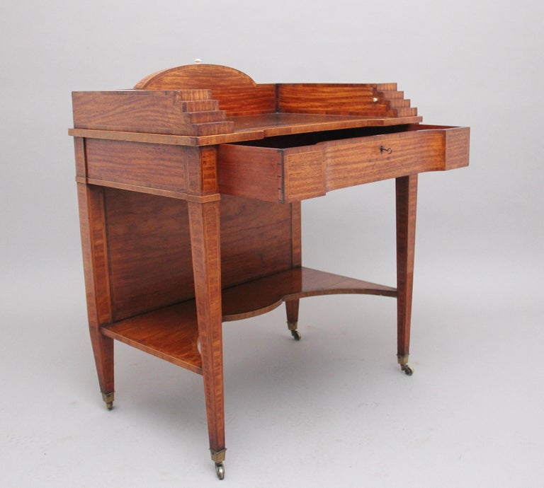 19th century satinwood ladies writing table in the Sheraton style, having a shaped leather writing surface decorated with blind tooling, decorative stepped sides which has secret pull out compartments either side to reveal a pen tray on one side and