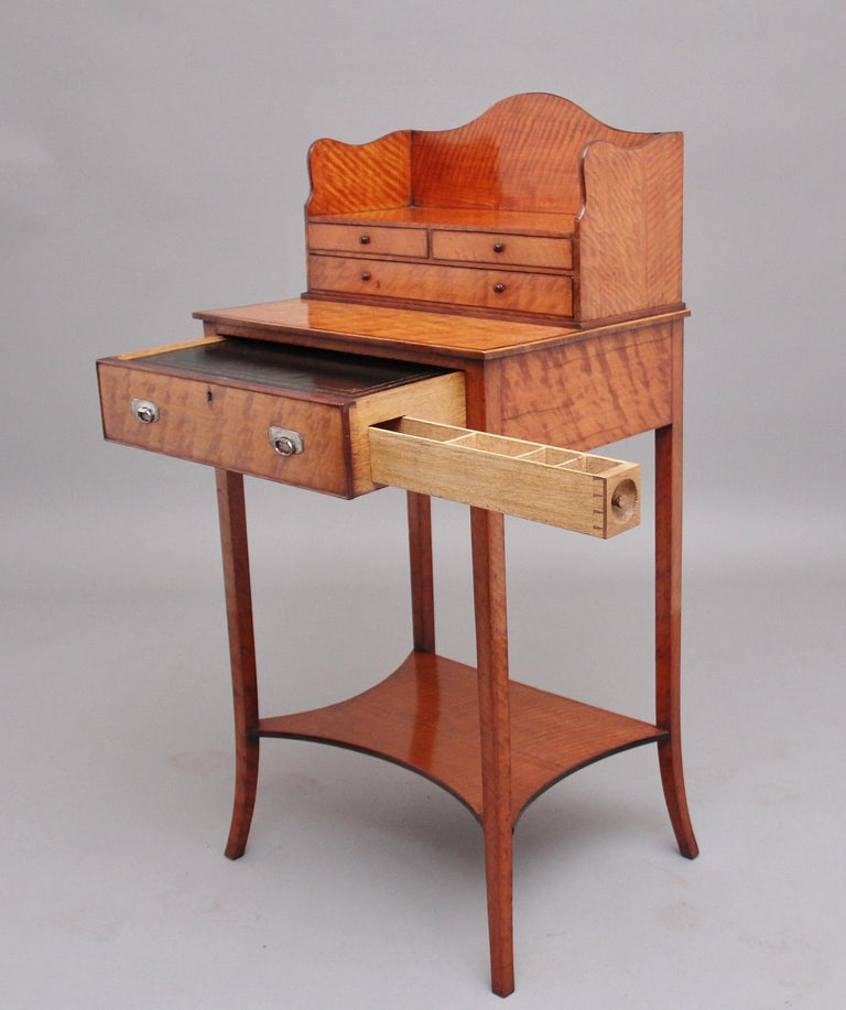 A super quality 19th century satinwood ladies writing table in the Sheraton style, having a shaped superstructure with two short over one long oak lined drawers with original turned wooden knob handles, the base section having a single drawer with
