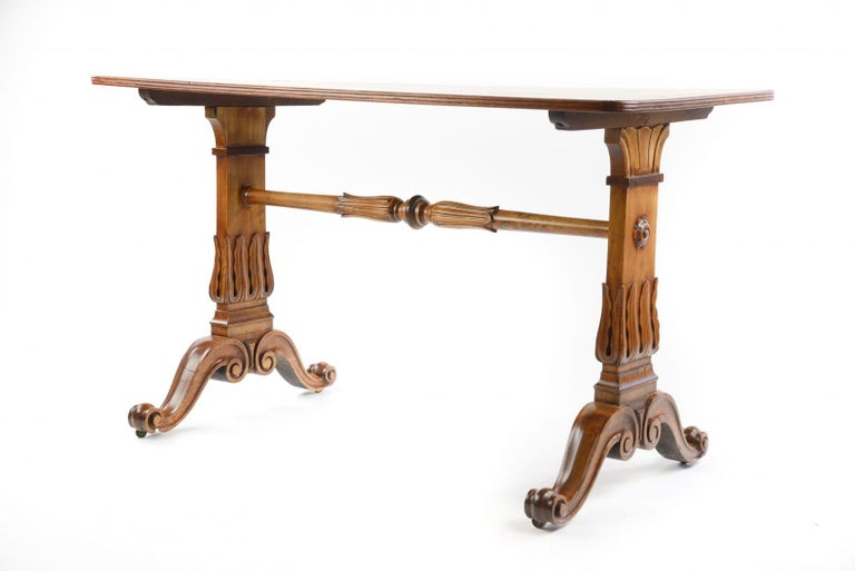 A 19th century satinwood rectangular library table, with stiff leaf carved trestle ends united by pole stretcher, on scrolling down-swept supports.