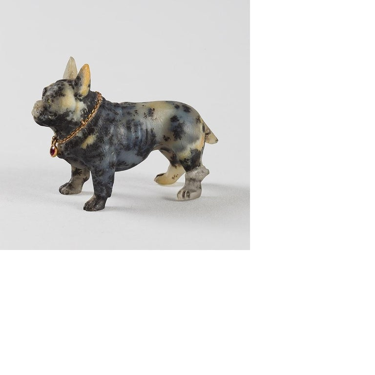 A late 19th century sculpture of a French bulldog, carved in white and black molted stone, with gold link collar adorned with red stone, and green stone eyes.