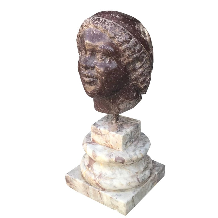 A head sculptured in Porphyry sitting on a Carrara marble column with a square step base, circa 19th century. In the style of Benvenuto Cellini, Italy.