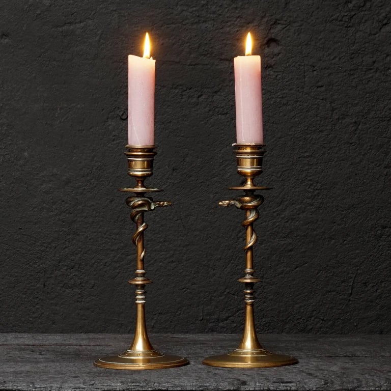 A pair of bronze candlesticks resting on a circular moulded base adorned with snakes crawling upwards. Marked F. Barbedienne on the base. Numbered 46244 underneath and signed.  Ferdinand Barbedienne (1810-1892) was a renowned French metalworker