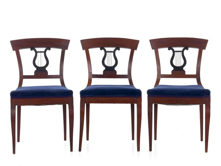 An attractive set of Biedermeier style walnut dining chairs, each is highlighted with an ebonized harp-form splat complete with strings of patinated copper. The bold molded crest rail is simple with its curved profile over the relatively complex