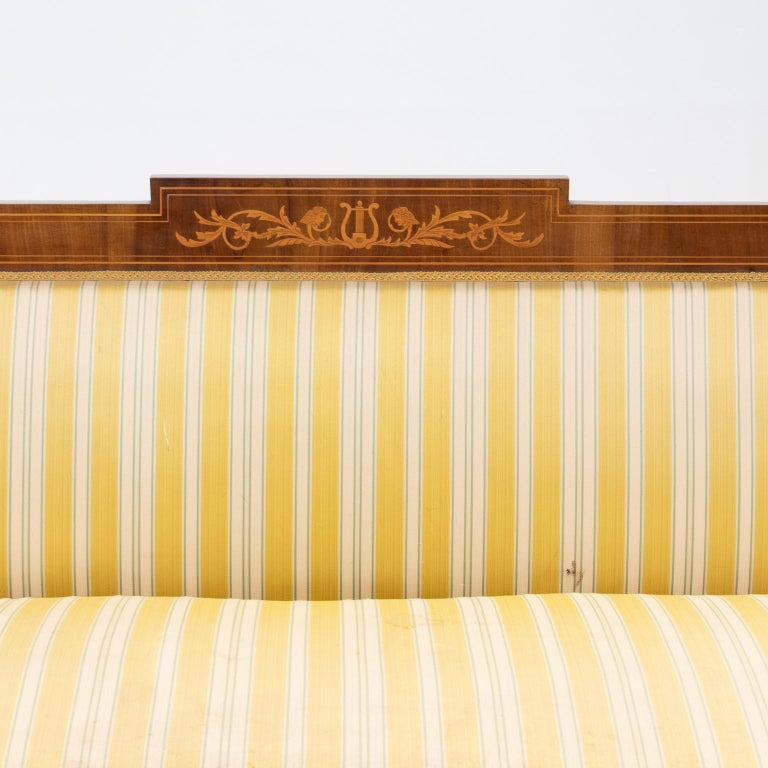 19th century Sheraton style sofa with inlay. The frame is mahogany and satinwood inlays. Notice the arms lift revealing compartments. Wonderful light patina developed on the mahogany. Structurally sound. Upholstery has some spots but easy to