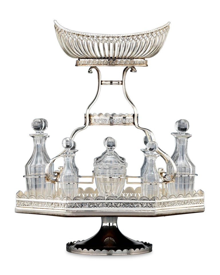 This elegant silver plate epergne is a rarity in that it also includes a full, cut-glass cruet set. This service's delicate central basket is elevated above a plateau holding ten finely-cut bottles, including two mustard pots, four small