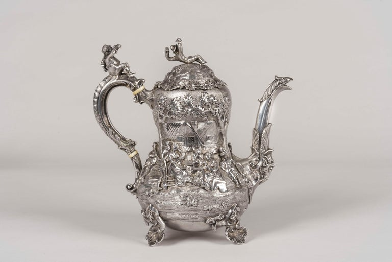 An exquisite tea & coffee service Made by Joseph Angell  Assayed in London in 1852-1853, the solid silver 4-piece service in the manner of Edward Farrell decorated in high relief with scenes of merry-making and tavern interiors in the style of