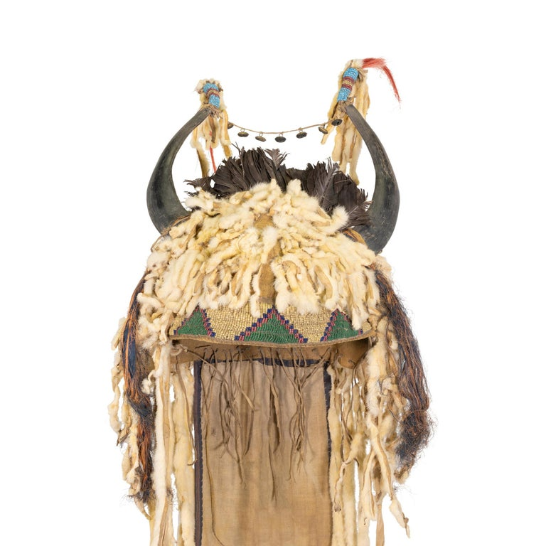 Genuine 19th Century Native American made Sioux split horn bonnet with buffalo hide liner. Long dangling ermine tails, tips beaded with greasy yellows and red hearts tipped with horse hair. Small brain tanned thong with hawk bells connecting both